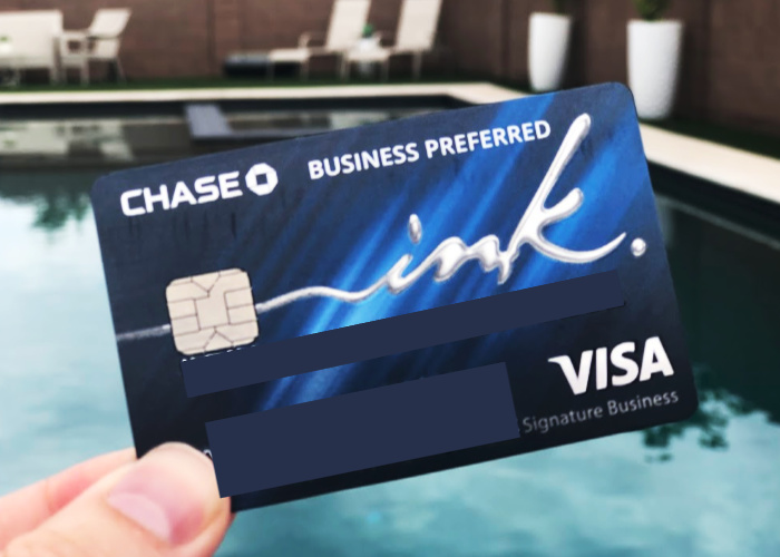 a hand holding a Chase Ink Business Preferred credit card with a pool in the background