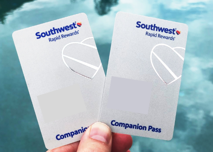 a hand holding two Southwest Airlines companion passes