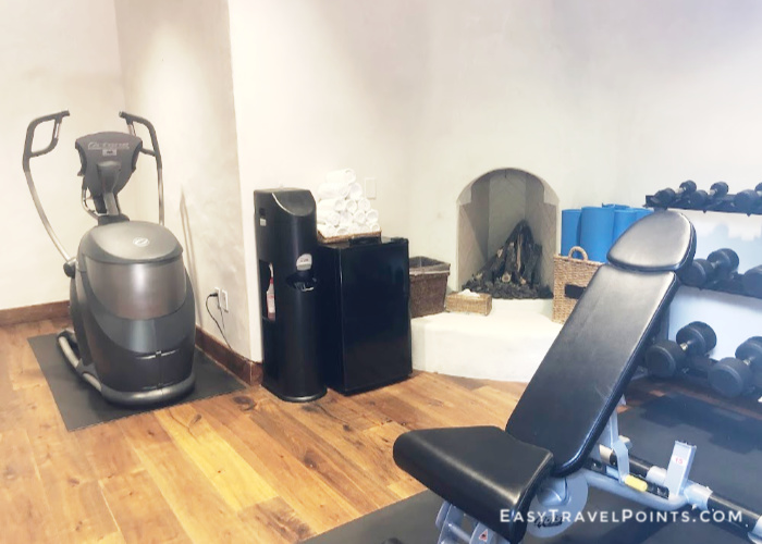 a small hotel fitness room with an some weights and an exercise machine