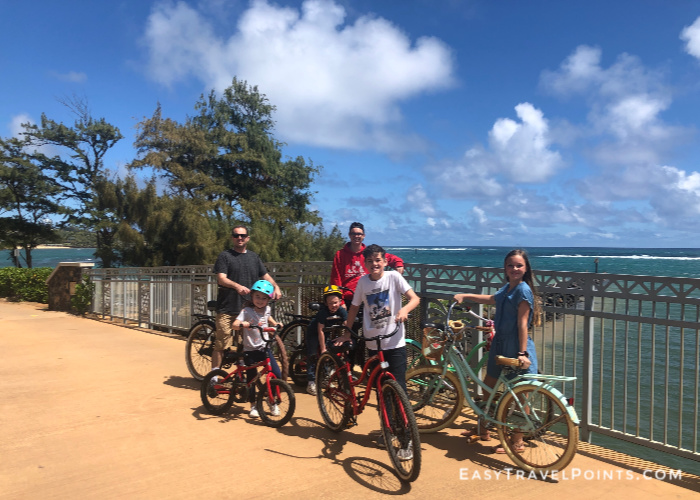 a father with his five kids on bikes with the ocean in the background