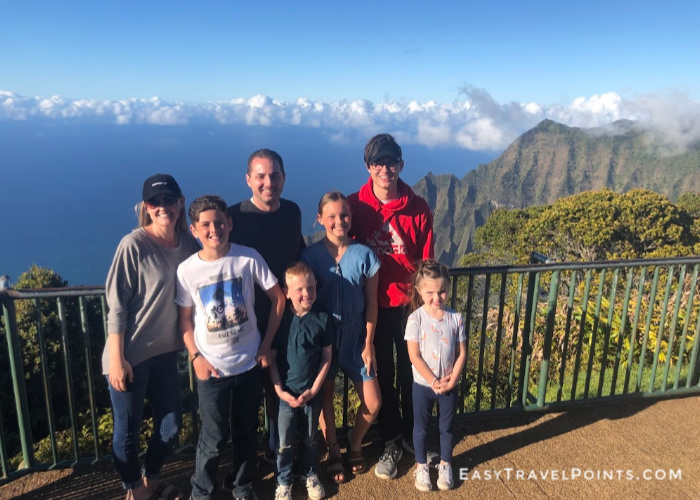 a family of 7 standing in front of the Kalalau Valley lookout in Kauai