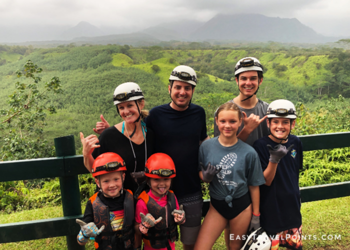 a family standing in front of a mountain in Kauai and all are wearing helmets and headlamps