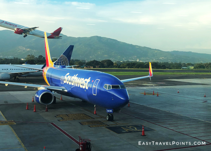 a southwest airlines boeing 737 parked at a gate in costa rica with an avianca airliner taking off behind it and a united airlines plane taxing on the tarmac