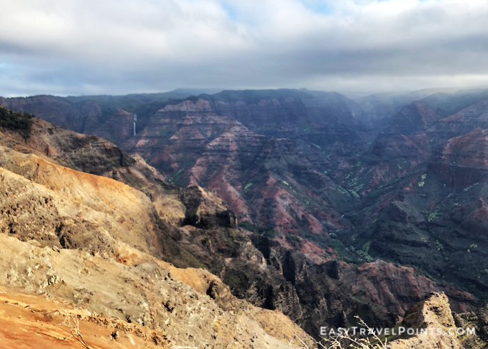 looking over Waimea Canyon in Kauai with a waterfall in the distance