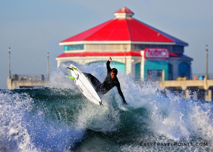 a man surfing in front of the HB pier