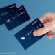 A hand holding a Capital One Venture credit card