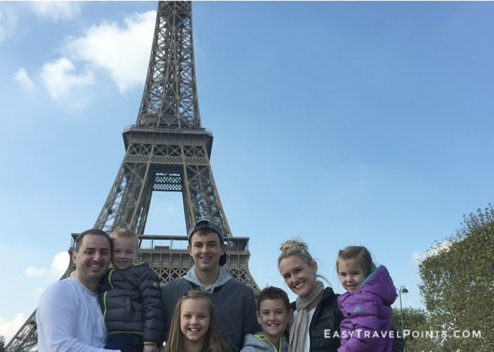 an attractive family in front of the Eiffel Tower