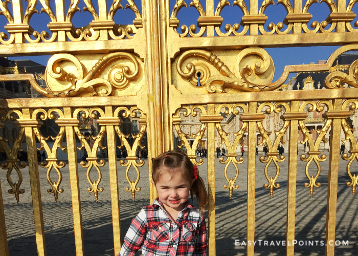 a cute little girl at the gate of the Palace of Versailles