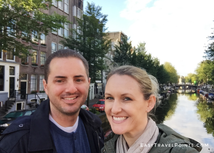 an attractive couple in front of a canal in Amsterdam