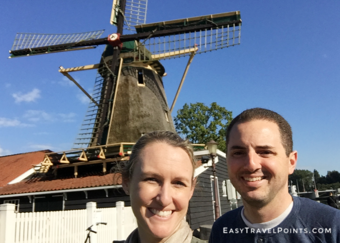an attractive couple in front of old windmill in Amsterdam